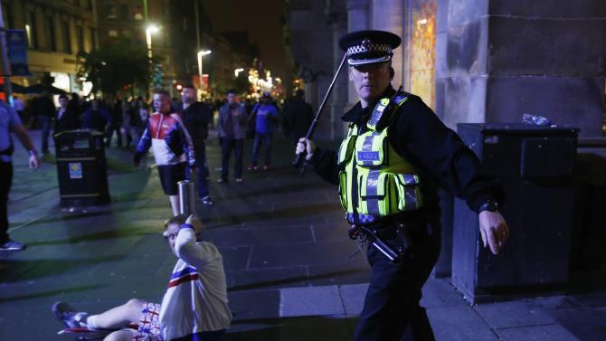 A policeman raises his baton as pro-union protestors clash with pro-independence protestors during a demonstration at George Square in Glasgow