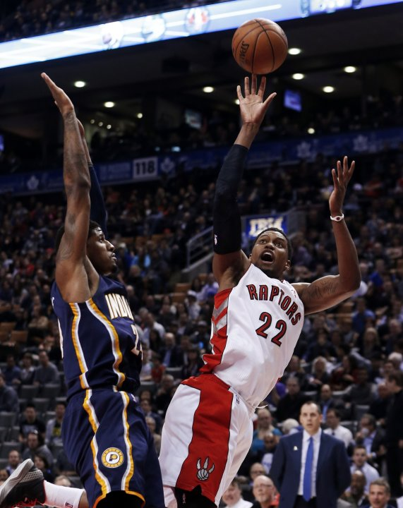 Raptors' Gay puts up a shot over Indiana Pacers' George during their NBA basketball game in Toronto