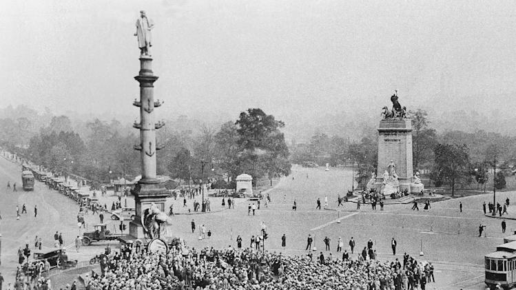 FILE - In an Oct. 12, 1933 file photo, about 1,000 people gather around the statue of Christopher Columbus high atop a six-story column in New York's Columbus Circle, to pay tribute to the great navigator on the 441st anniversary of his discovery of America. Japanese artist Tatzu Nishi has encased the 70-foot-tall column in scaffolding and is in the process of erecting a living room - complete with couch, coffee table and lamps - around the figure of Columbus. Some Italian-Americans say the art project makes a mockery of the great explorer and trivializes history. (AP Photo, File)