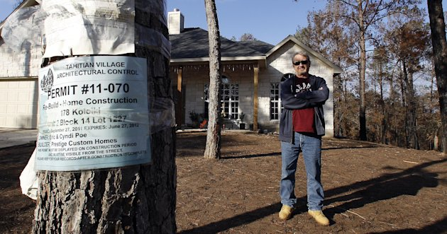In this Dec. 6, 2011 photo, Eric Poe stands in front of his new home, in Bastrop, Texas. The Poes lost their home to a Labor Day weekend wildfire and are one of the first to rebuild. (AP Photo/Eric Ga