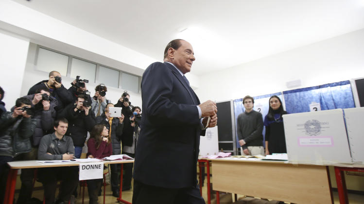 Former Premier Silvio Berlusconi casts his ballot in Milan, Italy, Sunday, Feb. 24, 2013. Italy votes in a watershed parliamentary election Sunday and Monday that could shape the future of one of Europe's biggest economies. (AP Photo/Antonio Calanni)