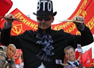 A Communist Party supporter holds puppets depicting Russian President Vladimir Putin (left) and Prime Minister Dmitry Medvedev (right) at a rally in Moscow last week against Russia&#39;s impending membership of the World Trade Organization