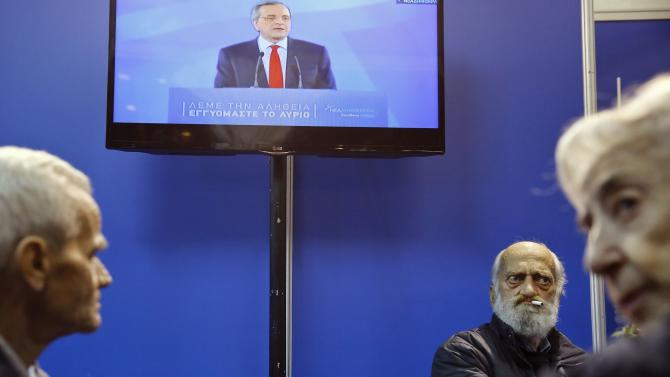 Supporters of Greece's New Democracy party wait for the exit poll results as PM Samaras is seen on a TV screen in Athens
