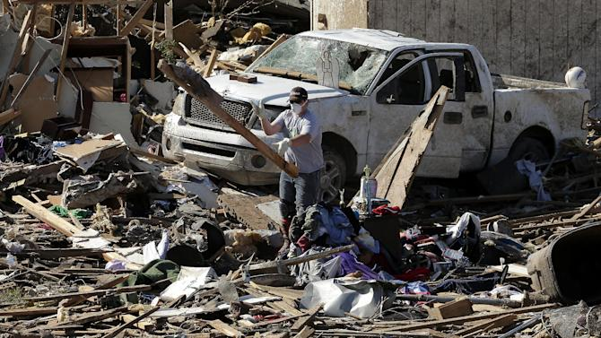 An unidentified man tosses a board as residents sort through their tornado-ravaged homes Wednesday, May 22, 2013, in Moore, Okla. Cleanup continues two days after a huge tornado roared through the Oklahoma City suburb, flattening a wide swath of homes and businesses. (AP Photo/Charlie Riedel)