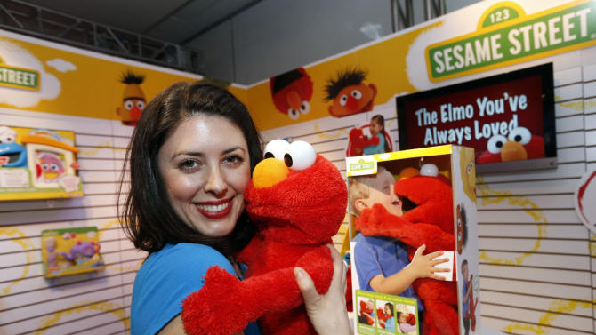 Demonstrator Patricia Santomasso welcomes BIG HUGS ELMO, Hasbro's first Elmo plush that really hugs kids back, to the PLAYSKOOL line with a hug in Hasbro's showroom at the American International Toy Fair, Friday, Feb. 8, 2013, in New York.  This cuddly 22-inch Elmo has flexible arms and a soft head to make him Hasbro's largest, cuddliest, most lifelike Elmo plush to date. (Photo by Jason DeCrow/Invision for Hasbro/AP Images)