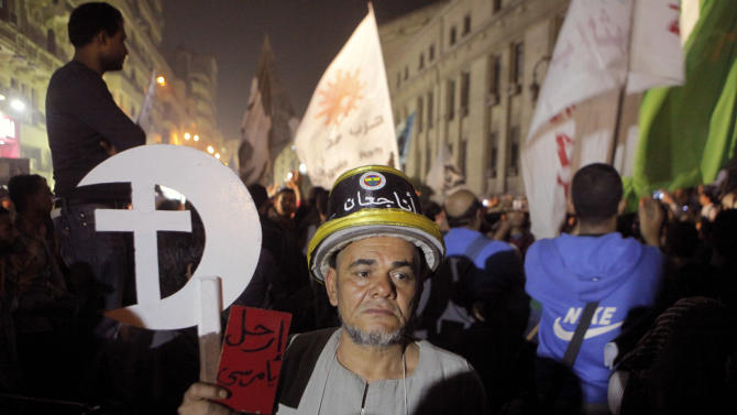 """Egyptian Samir Mancy, 60, holds a red card with Arabic reading, """"Morsi step down"""", during a rally in front of the general prosecutor's office in Cairo, Egypt, Saturday, April 6, 2013. Arabic on the hat reads, """"I'm hungry."""" Thousands of activists took to the streets Saturday to mark the fifth anniversary of the founding of a leading opposition group, the April 6 Youth Movement, and to push a long list of demands, including the formation of a more inclusive government amid a worsening economy. (AP Photo/Amr Nabil)"""