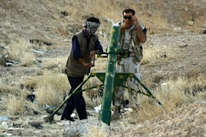Rebel fighters prepare to launch mortar rounds in the…