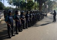 Bangladeshi police keep watch outside the International Crimes Tribunal court premises during a nationwide strike in Dhaka, on February 28, 2013. At least 34 people were killed in a wave of violence on Thursday as Islamists reacted furiously to a ruling that one of their leaders must hang for war crimes during the 1971 independence conflict