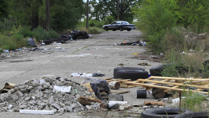 In a July 31, 2012 photo, a trashed strewn street is seen in east Detroit. Abandoned lots, alleys and neglected parks in Detroit used to be a favorite destination for discarded tires and trash. But over the past few months they have become dumping grounds for the dead. At least seven bodies have been found in some of the most desolated haunts in a half-empty city. (AP Photo/Carlos Osorio)