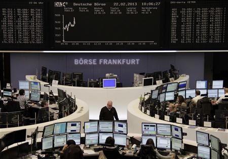 Traders are pictured at their desks in front of the DAX board at the Frankfurt stock exchange February 22, 2013. REUTERS/Remote/Lizza David (GERMANY - Tags: BUSINESS)