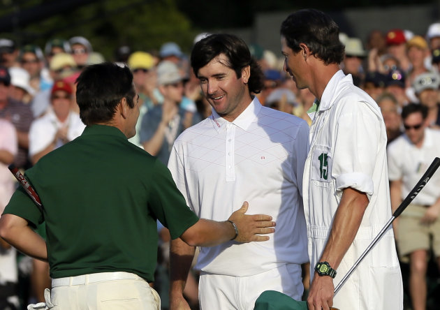 Louis Oosthuizen, left, of South Africa, congratulates Bubba Watson on the 18th green following their fourth round of the Masters golf tournament Sunday, April 8, 2012, in Augusta, Ga. At right is Wat