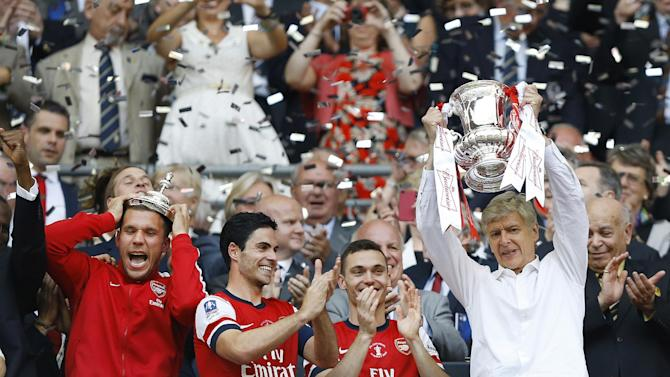 Arsenal's coach Arsene Wenger, right, hold the trophy aloft as he celebrates after his team won the English FA Cup final soccer match between Arsenal and Hull City at Wembley Stadium in London, Saturday, May 17, 2014. Arsenal won 3-2 after extra-time