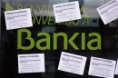 A man walks past a vandalized Bankia&#039;s bank office with papers stuck on it, in Barcelona