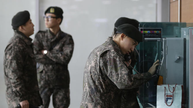 "South Korean soldiers use public phones after a report about a possible nuclear test conducted by North Korea, at the Seoul train station in Seoul, South Korea, Tuesday, Feb. 12, 2013. North Korea apparently conducted a widely anticipated nuclear test Tuesday, strongly indicated by an ""explosion-like"" earthquake that monitoring agencies around the globe said appeared to be unnatural. There was no confirmation from Pyongyang that it had conducted a test, which it has been threatening for weeks. (AP Photo/Lee Jin-man)"