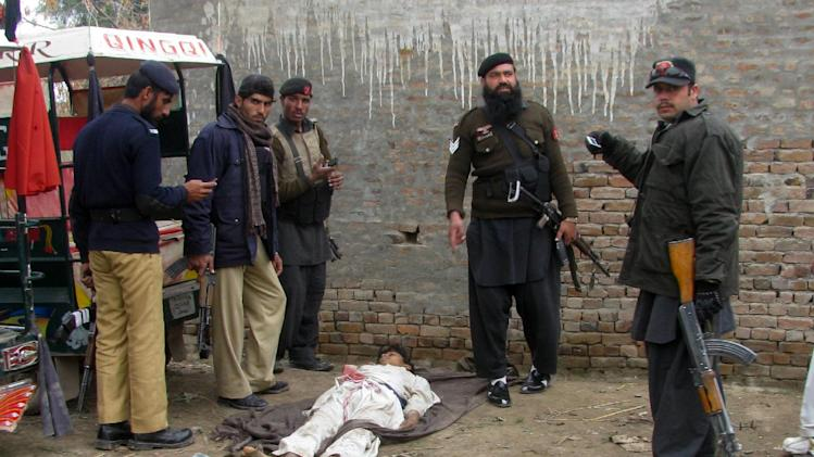 Police officers stand near a body of student killed during an attack by militants on police station in Bannu, Pakistan on Thursday, Feb. 14, 2013. Five suicide bombers attacked a police station in the country's northwestern city of Bannu, wounding a police officer. The city's police chief Nisar Tanoli said three of the bombers detonated their explosives vests while the police shot dead the other two. (AP Photo/Ijaz Muhammad)