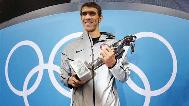 Michael Phelps with his trophy awarded to him by FINA honouring him as the most decorated Olympian of all time (Reuters)