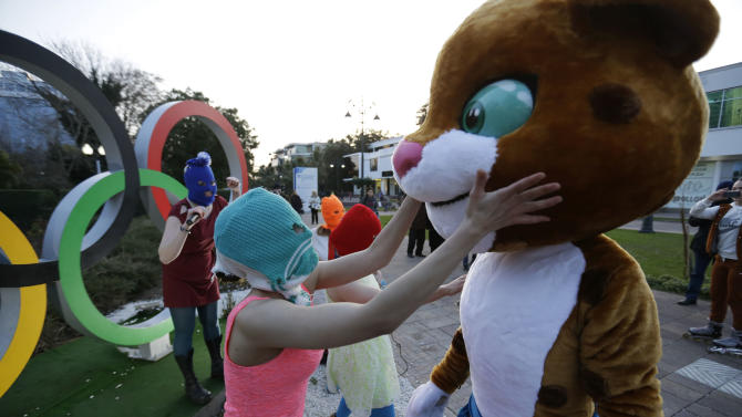 Pussy Riot member Nadezhda Tolokonnikova in the aqua balaclava, left, interacts with an Olympic mascot while the group perform next to the Olympic rings in Sochi, Russia, on Wednesday, Feb. 19, 2014. Cossack militia attacked the punk group with horsewhips earlier in the day as the artists - who have feuded with Vladmir Putin's government for years - tried to perform under a sign advertising the Sochi Olympics. (AP Photo/David Goldman)