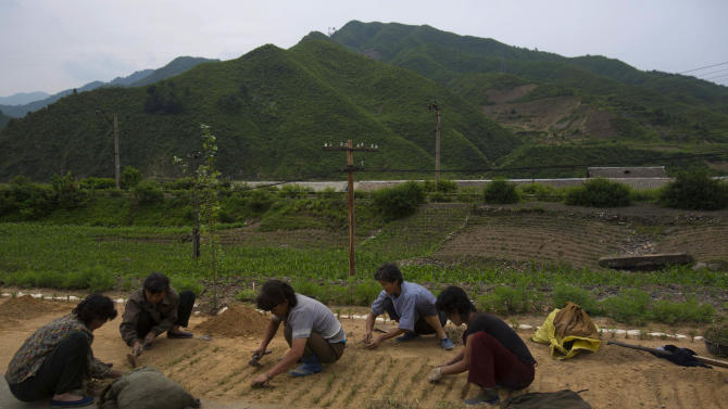 FILE - In this Thursday, June 14, 2012 file photo, North Korean women work on a roadside in North Phyongan Province, North Korea. North Korea increased its staple foods production for the second year in a row but its citizens are still suffering from a serious lack of key proteins and fats in their diets, a U.N. report said Monday, Nov. 12, 2012. A U.N. team visited all nine agricultural provinces of the communist state in September and October during the main cereal harvest and estimated that even with the increase - a 10 percent improvement over last year - North Korea will need to import 507,000 metric tons of cereals to meet its basic food needs. (AP Photo/David Guttenfelder, File)
