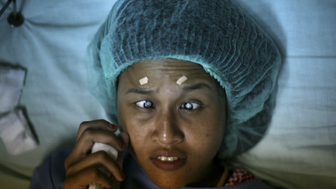 In this Tuesday, Nov. 13, 2012 photo, 20-year-old patient Ayu Pratiwi who has been blind since she was 10 lies on a bed as she waits for her cataract surgery at Putri Hijau military hospital in Medan, North Sumatra, Indonesia. Indonesians flocked to the hospital for free cataract surgery performed by a team led by Nepalese master surgeon Dr. Sanduk Ruit who is renowned for his high-volume assembly-line approach. During the eight-day eye camps held in two towns in North Sumatra, more than 1,400 cataracts were removed. (AP Photo/Binsar Bakkara)