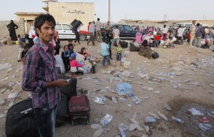 Syrian refugees wait for buses after crossing the border…