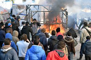 "A shack burns in the ""Jungle"" migrant camp …"