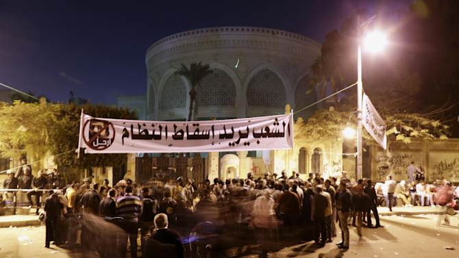 """Egyptian protesters chant anti-Muslim Brotherhood and Egyptian President Mohammed Morsi slogans outside the presidential palace, background, under a banner with a defaced picture of President Mohammed Morsi and Arabic that reads """"the people want to bring down the regime,"""" in Cairo, Egypt, Saturday, Dec. 8, 2012. Egypt's military warned on Saturday of """"disastrous consequences"""" if the crisis that sent tens of thousands of protesters back into the streets is not resolved, signaling the army's return to an increasingly polarized and violent political scene.(AP Photo/Hassan Ammar)"""