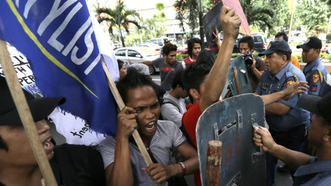 CORRECTS BYLINE TITLE AND SOURCE - Police push back protesters as they attempt to hold a rally outside the U.S. Embassy in Manila to protest the recent incident in the Philippines wherein a U.S. Navy minesweeper, USS Guardian, ran aground off Tubbataha Reef, a World Heritage Site in the Sulu Sea, 640 kilometers (400 miles) southwest of Manila, Philippines Saturday Jan. 19, 2013. The protesters are demanding the abrogation of the Visiting Forces Agreement which allows U.S. troops' presence in the country.  (AP Photo/Bullit Marquez)