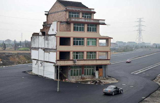 An isolated house sits in the middle of a newly built road, because a Chinese couple refused to sign an agreement allowing for their home to be demolished (Rex)
