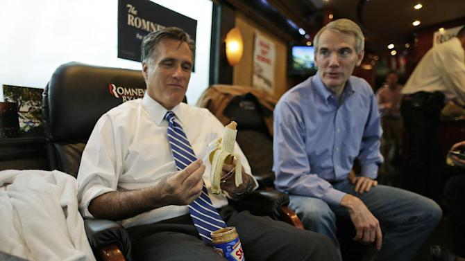 Republican presidential candidate and former Massachusetts Gov. Mitt Romney puts peanut butter on a banana as he rides his campaign bus with Sen. Rob Portman, R-Ohio, en route to Celina, Ohio for a campaign rally, Sunday, Oct. 28, 2012. (AP Photo/Charles Dharapak)