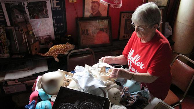 Marcy Skowronski, 87, looks through a pile of bras Friday, May 17, 2013, in Milwaukee that used hang from the ceiling of her bar, Holler House. The city told her recently they were a fire hazard and ordered them to be taken down but later backed down after the newspaper and an alderman got involved.  (AP Photo/Carrie Antlfinger)