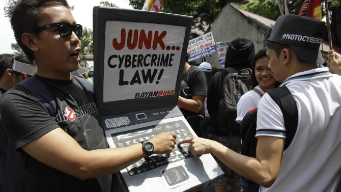 A protester holds a mock laptop during a rally against the anti-cybercrime law in front of the Supreme Court in Manila, Philippines, Tuesday Oct. 9, 2012. The Philippine Supreme Court on Tuesday suspended implementation of the country's anti-cybercrime law while it decides whether certain provisions violate civil liberties. The law aims to combat Internet crimes such as hacking, identity theft, spamming, cybersex and online child pornography. (AP Photo/Aaron Favila)
