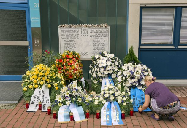 A woman lights candles in front of wreaths at a memorial at the former accommodation building of the Israeli Olympic team in Munich, southern Germany, Wednesday, Sept. 5, 2012, during a commemoration
