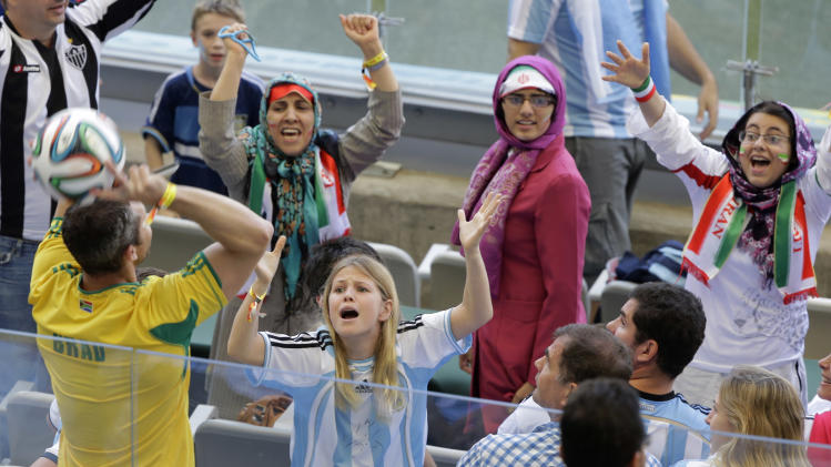 Argentine and Iran's fans ask another spectator for the ball to during the group F World Cup soccer match between Argentina and Iran at the Mineirao Stadium in Belo Horizonte, Brazil, Saturday, June 21, 2014. (AP Photo/Sergei Grits)