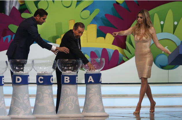 Former soccer great and World Cup winner Alcides Ghiggia of Uruguay is supported by former World Cup player Fernando Hierro of Spain, left, and Brazilian actress Fernanda Lima, right, during the draw