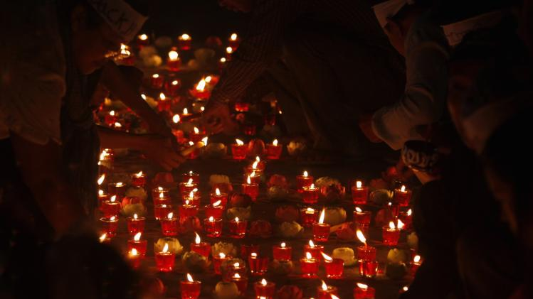 Residents of Boeung Kak Lake light candles during Buddhist ceremony praying for release of 21 detainees jailed and to pray for missing Malaysia Airlines MH370, in Phnom Penh