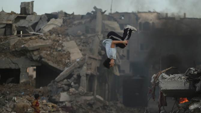 A Palestinian youth practices his Parkour skills over the ruins of houses in the Shejaia neighborhood east of Gaza City