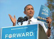 US President Barack Obama shows a copy of his jobs plan during a campaign rally October 23, at Triangle Park in Dayton, Ohio. Republican White House hopeful Mitt Romney said Obama&#39;s campaign was &quot;taking on water&quot; Tuesday, as the rivals barnstormed across toss-up states while seeking swing votes two weeks before election day