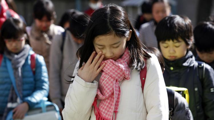Students observe a moment of silence to pay tribute to the victims of the March 11, 2011 earthquake and tsunami during an earthquake simulation exercise at an elementary school in Tokyo
