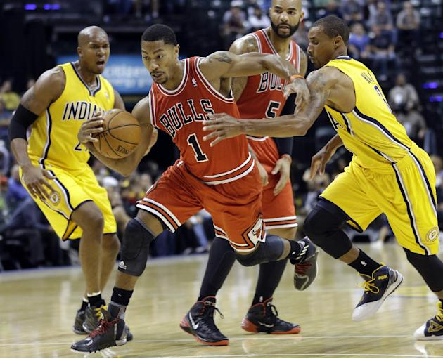Chicago Bulls guard Derrick Rose, center, cuts between Indiana Pacers guard George Hill, right, and power forward David West, left, in the first half of an NBA preseason basketball game in Indianapoli