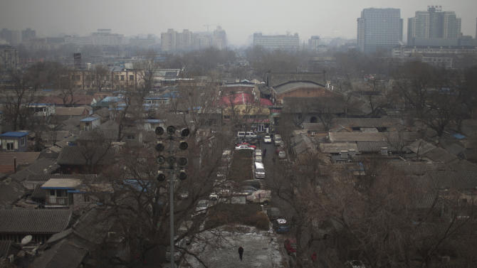 "In this Jan. 15, 2013 photo, a resident, bottom, walks in a ""hutong"" neighborhood behind the Drum Tower and the Bell Tower in central Beijing, China. The district government wants to demolish these dwellings, move their occupants to bigger apartments farther from the city center and redevelop a square in 18th century Qing Dynasty fashion.  (AP Photo/Alexander F. Yuan)"