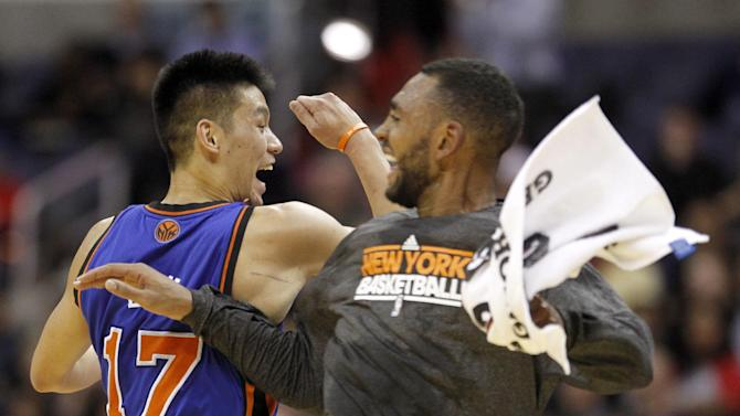 New York Knicks guard Jeremy Lin (17) celebrates with teammate Jared Jeffries during a timeout against the Washington Wizards during the first half of an NBA basketball game, Wednesday, Feb. 8, 2012, in Washington. (AP Photo/Haraz N. Ghanbari)
