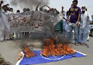 Protesters shout slogans beside a burning NATO flag during a demonstration against drone attacks, in Multan, on June 27. There has been a dramatic increase in US drone strikes in Pakistan since May when a NATO summit in Chicago could not strike a deal to end a six-month blockade on NATO supplies crossing into Afghanistan