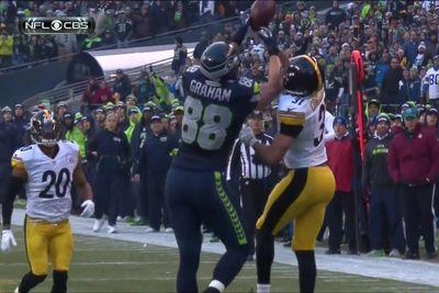 Jimmy Graham hauls in a leaping, juggling catch despite the efforts of two defenders