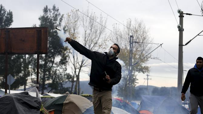 A stranded migrant throws a tear gas canister back to Macedonian police officers as they clashed after a migrant was injured when he climbed on top of a train wagon, near the village of Idomeni