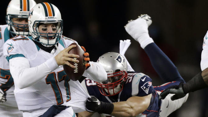 New England Patriots defensive end Trevor Scott (99) tries to tackle Miami Dolphins quarterback Ryan Tannehill (17) during the third quarter of an NFL football game in Foxborough, Mass., Sunday, Dec. 30, 2012. (AP Photo/Charles Krupa)