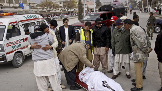 People look at the lifeless body of a government official killed in Quetta, Pakistan, Monday, Dec. 17, 2012. Gunmen killed a provincial government spokesman in the southwest Pakistan in an apparent sectarian attack, and then shot to death two nearby policemen, police said. (AP Photo/Arshad Butt)
