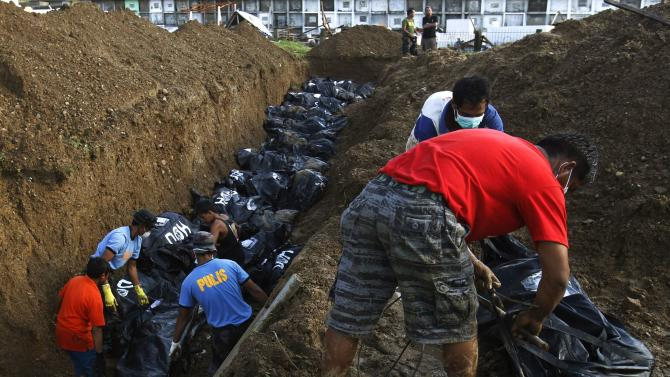 People carry body bags to a mass grave for burial in the aftermath of super typhoon Haiyan in Tacloban