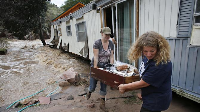 "FILE - In this Sept. 13, 2013 file photo, water rushes through her destroyed home as resident Holly Robb, left, and her neighbor Pam Bowers salvage belongings after storms that raged through the Rocky Mountain foothills in this photo made in Lyons, Colo. Two low-lying trailer parks in the small town, 20 minutes to the north of Boulder, bore the brunt of the recent flooding. ""I don't think we'll ever be able to go back,"" said Robb. (AP Photo/Brennan Linsley, File)"
