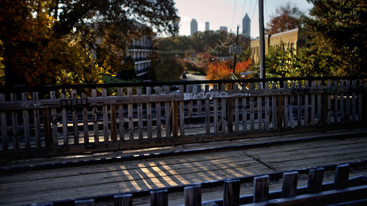 In this Nov. 20, 2012 photo, a section of old rail tracks is preserved next to the Atlanta BeltLine as the midtown skyline stands in the background in Atlanta. Since an Atlanta nonprofit opened a 2.25-mile-long paved trail east of downtown last month, it has attracted a steady stream of joggers, dog-walkers and cyclists to take in spectacular views of the skyline as well as a slice of established neighborhoods that were once only seen by riding a freight train. The Eastside Trail is the latest and most visible phase of the Atlanta BeltLine, an ambitious $2.8 billion plan to transform a 22-mile railroad corridor that encircles Atlanta into a network of parks, trails, public art, affordable homes and ultimately streetcars. (AP Photo/David Goldman)