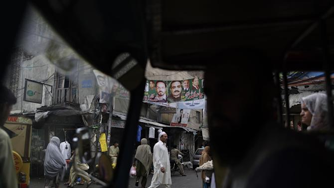 With an election banner showing former prime minister and leader of Pakistan Muslim League-N, Nawaz Sharif, and other members of his party, top center, Pakistanis are seen through a rickshaw waiting for the traffic to move, in Rawalpindi, Pakistan, Sunday, May 12, 2013. Pakistan's former prime minister Nawaz Sharif looked set Sunday to return to power for a third term, with an overwhelming election tally that just weeks ago seemed out of reach for a man who had been ousted by a coup and was exiled abroad before clawing his way back as an opposition leader. (AP Photo/Muhammed Muheisen)
